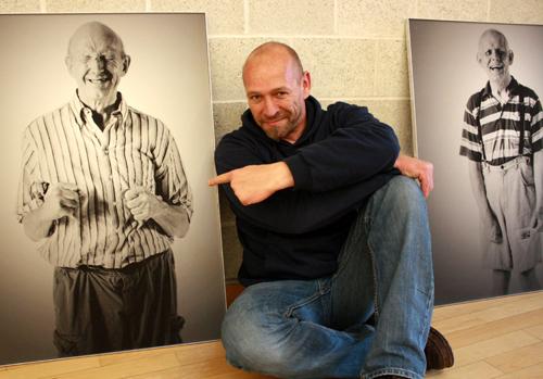 """Andreas Reinern zwischen Bildern seiner Ausstellung """"SichtlichMensch – Menschen mit Behinderung fotografieren Menschen mit Behinderung"""""""
