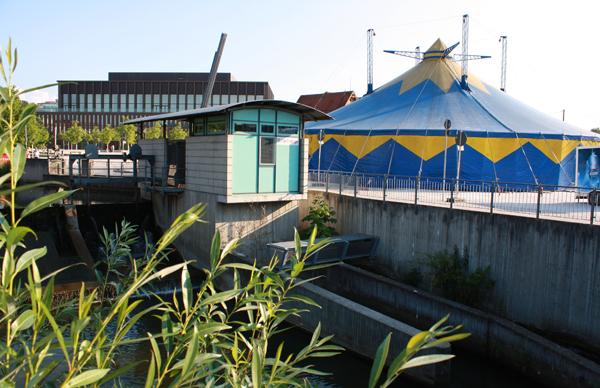 Direkt neben dem Echaz-Wehr am Bürgerpark hat das Festivalzelt seinen Platz, dahinter die neue Reutlinger Stadthalle. [Foto: Gerhard Schindler]