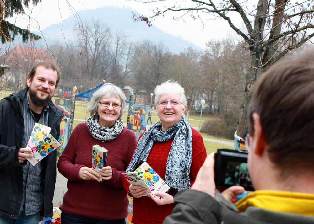 Gruppenbild mit Hausberg: Während sich die Achalm in Grau hüllt, halten (von links) Markus Christ, Rose Henes und Elisabeth Braun den farbenfrohen Festival-Flyer in die Kamera.